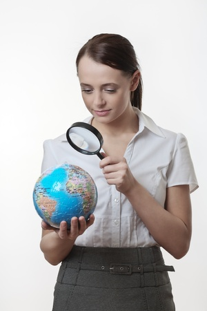 woman holding up a jigsaw globe puzzle and looking at it with a inspecting eye with a magnifying glass Stock Photo - 17079719