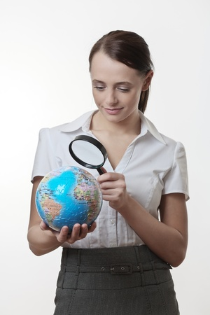 woman holding up a jigsaw globe puzzle and looking at it with a inspecting eye with a magnifying glass Stock Photo - 17079716