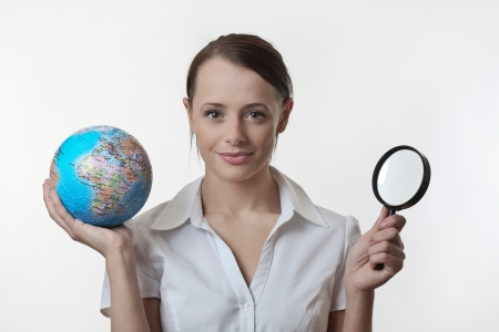 woman holding up a jigsaw globe puzzle and a magnifying glass Stock Photo - 17079774