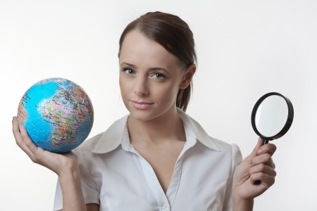 woman holding up a jigsaw globe puzzle and a magnifying glass Stock Photo - 17079771