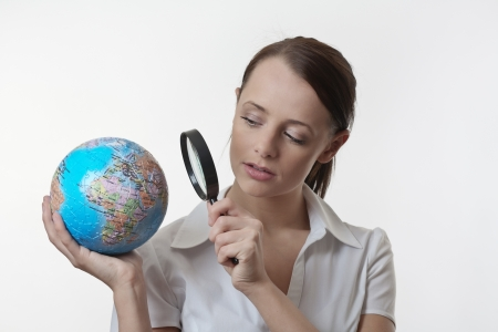 woman holding up a jigsaw globe puzzle and looking at it with a inspecting eye with a magnifying glass Stock Photo - 17079776