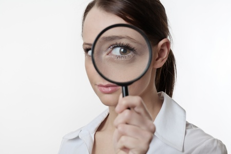 Confident young woman looking through a magnifying glass Stock Photo