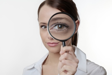 Confident young woman looking through a magnifying glass Stock Photo - 17079915