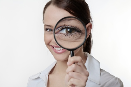 Confident young woman looking through a magnifying glass Stock Photo - 17079895