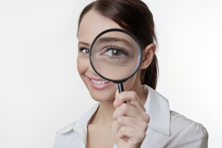 Confident young woman looking through a magnifying glass Stock Photo - 17079856