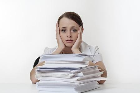Een beklemtoonde vrouw met haar hoofd in haar handen, zittend aan haar bureau met een grote stapel van papierwerk gestapeld in de voorkant van haar.