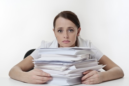 A stressed female, sitting at her desk with a large pile of papers stack in front of her  photo