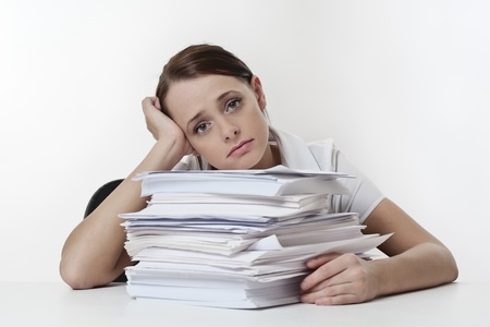 A stressed female, sitting at her desk with a large pile of papers stack in front of her  Stock Photo