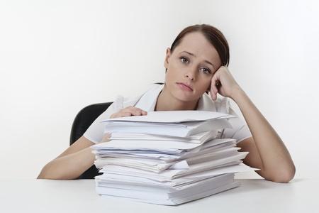 Een gestresst vrouw, zit aan haar bureau met een grote stapel papieren stapel voor haar