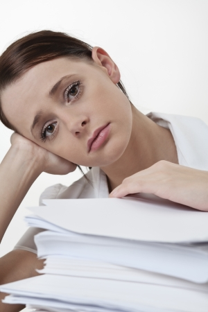 A stressed female, sitting at her desk with a large pile of papers stack in front of her  Stock Photo - 17079780