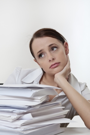 A stressed female, sitting at her desk with a large pile of papers stack in front of her  Stock Photo - 17079809
