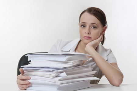 A stressed female, sitting at her desk with a large pile of papers stack in front of her Stock Photo - 17079879