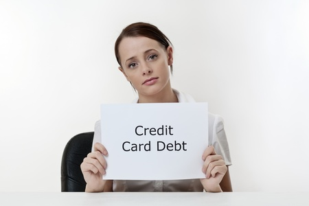 credit card debt: woman sitting at a desk worried about credit card debt problems