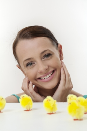 attractive women looking over a white table top at a group of model little easter chickens Stock Photo - 17079806