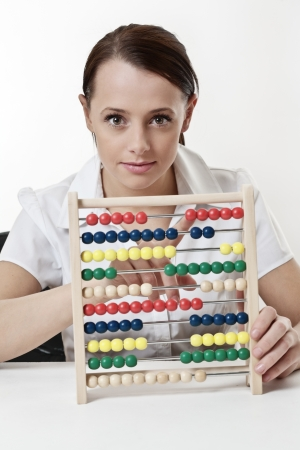 sums: young attractive woman using a wooden abacus to count and add up her sums