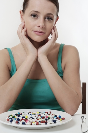 taking pill: woman sitting at a table about to eat a plate full of pills