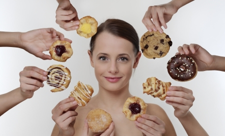 woman surrounded by many hands holding cream cakes with so much choice and temptation is she going to forget about her diet and indulge herself  Stock Photo