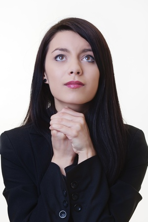 woman with her hands together by her face in thoughtful prayer Stock Photo - 17456501