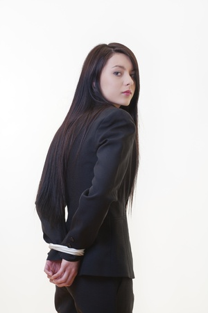 bound woman: woman dressed in a business suit with her hand tied up behind her back