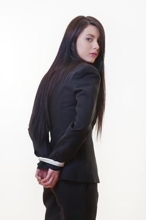 彼女の手後ろ手に縛らでビジネス スーツに身を包んだ女性 写真素材