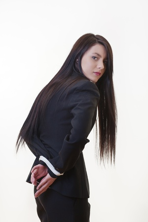 woman dressed in a business suit with her hand tied up behind her back photo