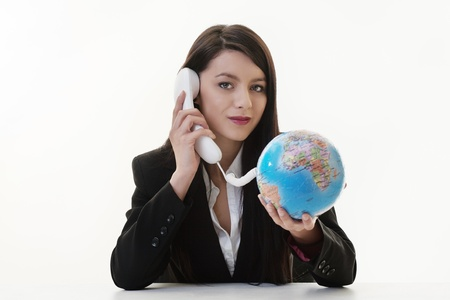woman using a phone and the cord connected to a globe photo
