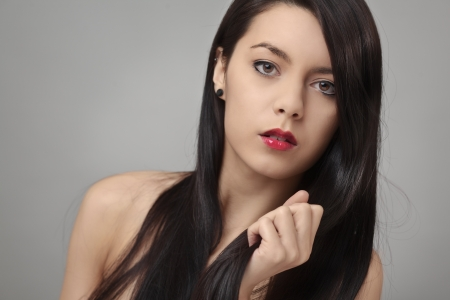 Pretty woman with long straight hair looking at camera grabbing her har with hand Stock Photo - 17546098
