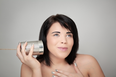 portrait of young woman hearing through a tin can  Stock Photo - 18036398