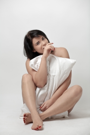 Woman holding a pillow sitting on a white studio floor photo
