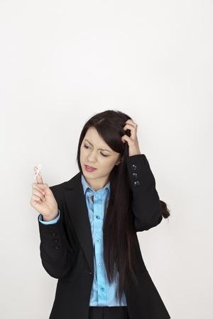 przypominać: kobieta z Å'uku smyczkowy przywiÄ…zany do palca, aby przypomnieć jej coÅ› zrobić w pracy Zdjęcie Seryjne