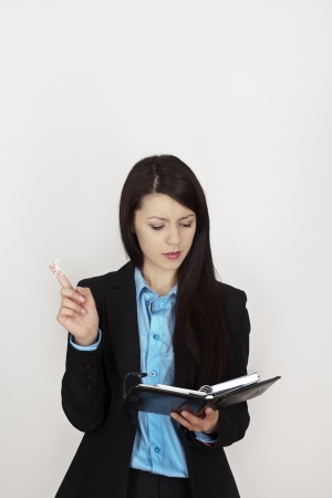 business woman with string bow tied to her finger to remind her to do something at work, looking in her filofax trying to find out what it could be photo