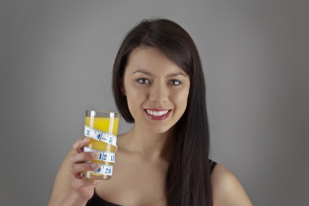 replenishing: An attractive young woman drinking orange juice from a glass with a tape measure wrapped around glass