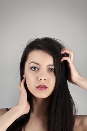 woman grabbing her hair in on grey studio background photo