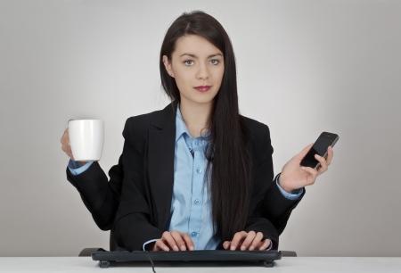 vrouw zit aan haar bureau met vier armen twee handen te typen op een toetsenbord en een met een mobiele telefoon en het andere een kop koffie of thee