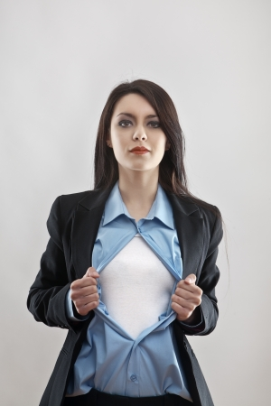 떨어져 슈퍼 히어로 사업가 포즈를 하 고 그녀의 셔츠를 잡아 당기는 매력적인 사업가