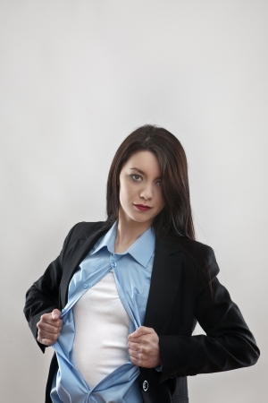 attractive businesswoman pulling her shirt apart doing a superhero businessman poses photo