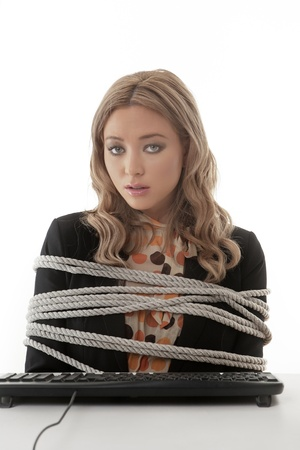 tied girl: Business woman tires up to her desk unable to type Stock Photo