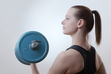 sexy fitness woman lifting weights shot in the studio photo