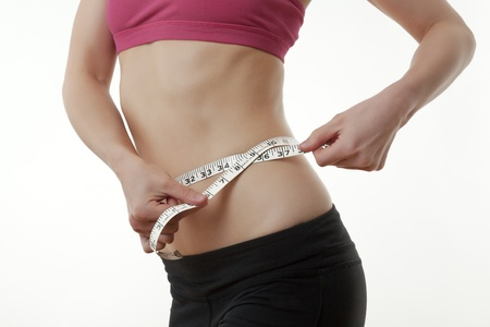 womans hand measuring her waist photo