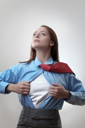 매력적인 사업가 슈퍼 히어로 사업가 포즈를 떨어져 그녀의 셔츠를 당겨 일