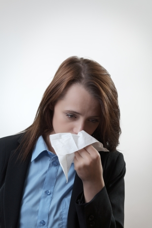 Businesswoman blowing her nose flu going around at work Stock Photo - 22685481