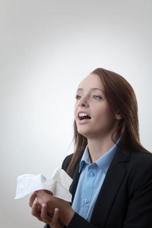 Businesswoman blowing her nose flu going around at work Stock Photo - 22685482