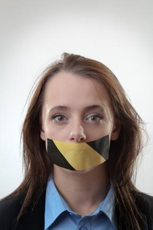 kokhalzen: Een beeld van een jonge vrouw met een tape op haar mond Stockfoto