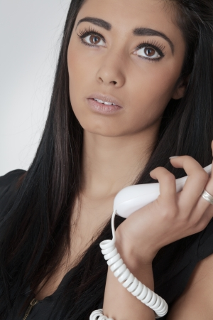 asian woman not look very happy with the telephone cord wrapped around her arm photo