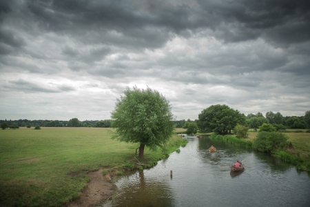looming: Overcast sky looming over a stream with 2 rowing boats rowing down the stream Stock Photo