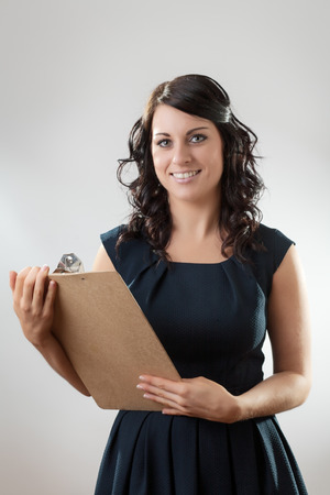 Portrait of an elegant young businesswoman with clipboard photo