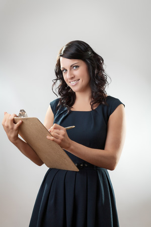 Portrait of an elegant young businesswoman with clipboard and pen photo