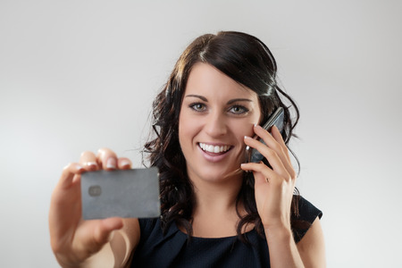Beautiful woman holding a credit card on the phone maybe she's buying something Stock Photo - 26001443