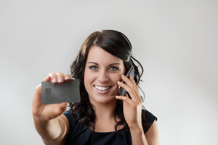 Beautiful woman holding a credit card on the phone maybe she's buying something Stock Photo - 26001444