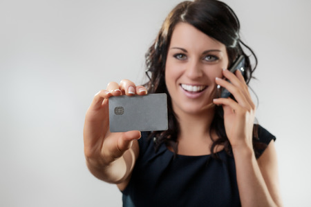 Beautiful woman holding a credit card on the phone maybe shes buying something photo